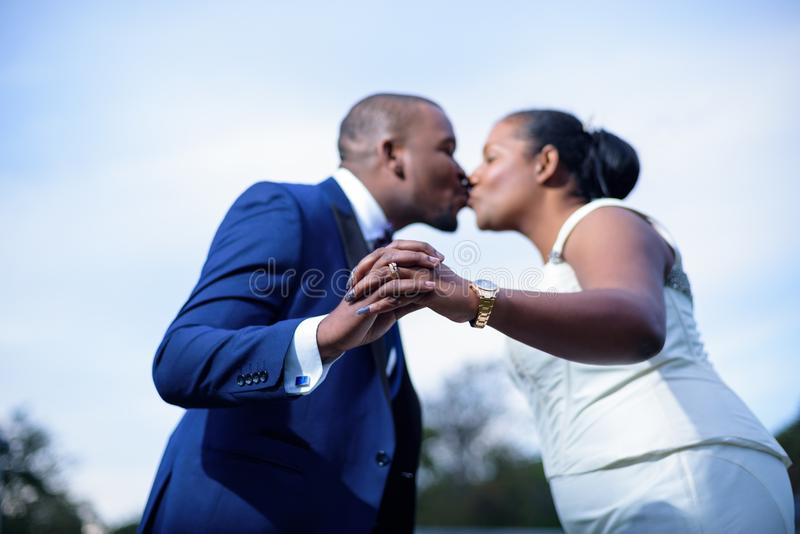 Newlyweds kissing while showing wedding rings. In focus with the couple out of focus stock images