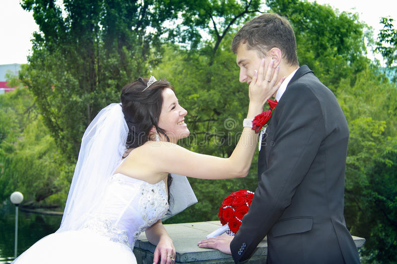 Newlyweds looking to each other with love. Sweet newlyweds looking to each other with love and embracing stock images