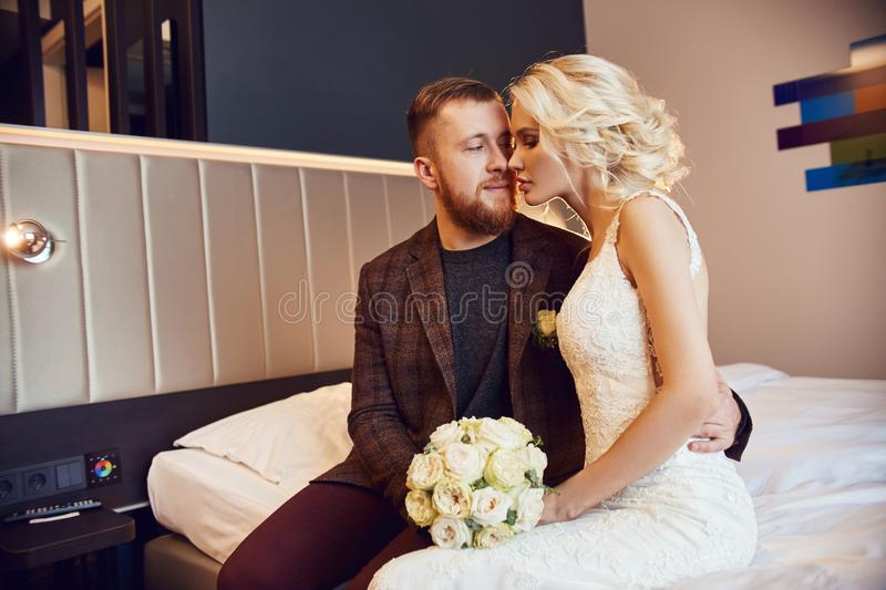Newlyweds in the morning in the hotel room sitting on the bed hugging and looking at each other in anticipation of the wedding. Ceremony. Bearded hipster groom royalty free stock photo