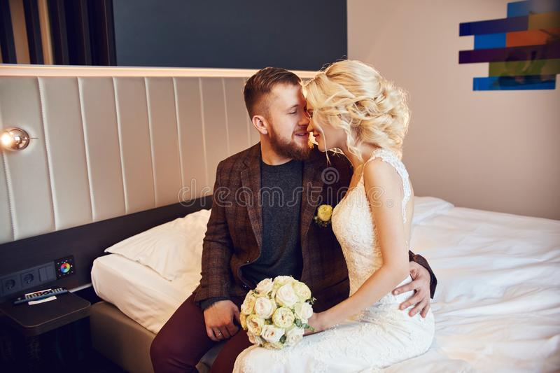 Newlyweds in the morning in the hotel room sitting on the bed hugging and looking at each other in anticipation of the wedding. Ceremony. Bearded hipster groom stock photo