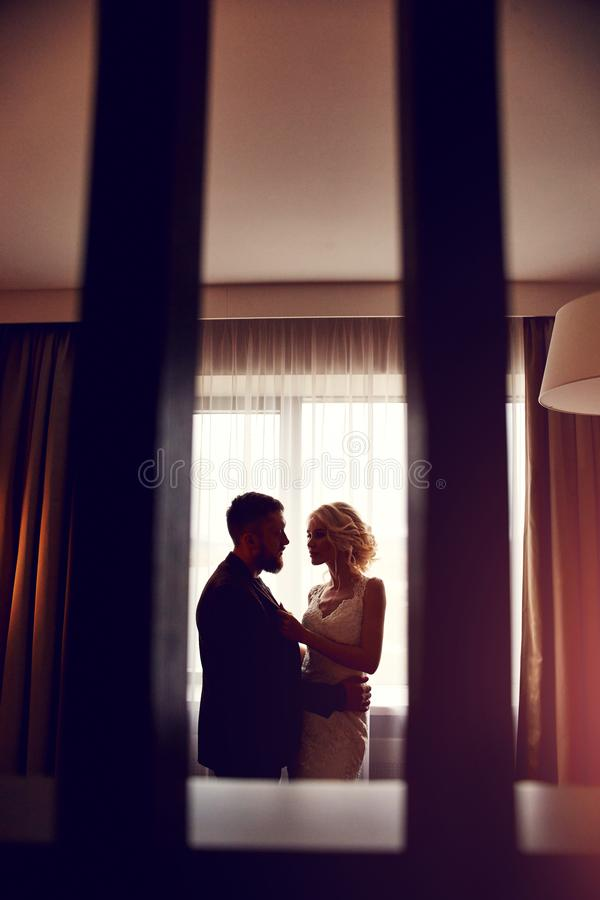 Newlyweds in the morning in the hotel room sitting on the bed hugging and looking at each other in anticipation of the wedding. Ceremony. Bearded hipster groom royalty free stock image