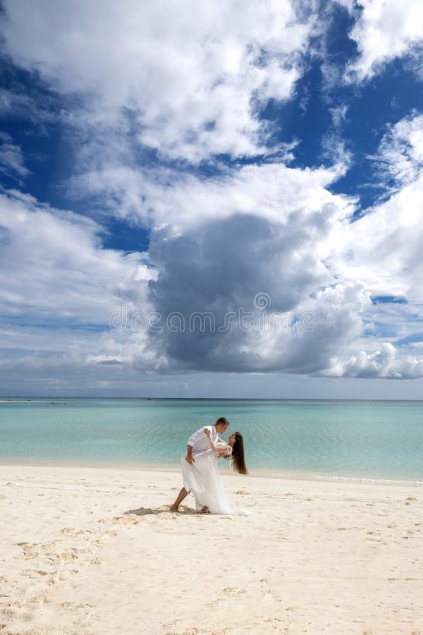 Perfect wedding. Newlyweds are passionately dancing on a gorgeous beach with white sand and turquoise water royalty free stock photos