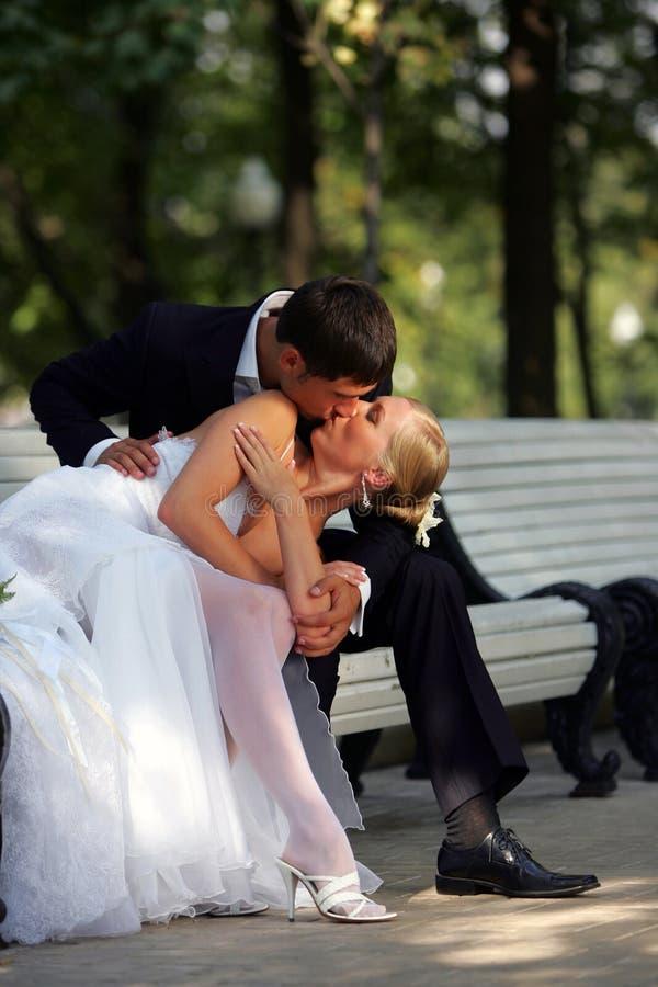 Newlyweds que beijam no banco de parque fotos de stock royalty free