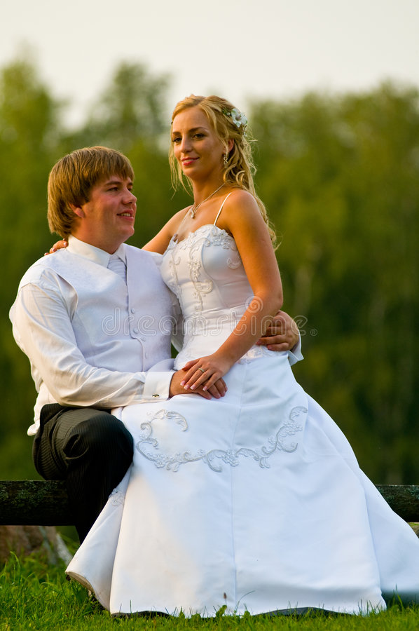 Newlyweds que sentam-se no banco fotografia de stock royalty free