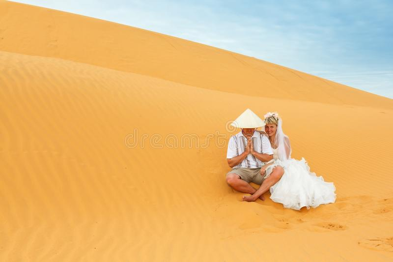 Newlyweds in the sand dunes in Vietnam. Young bride in white dress, on the man national hat royalty free stock photo