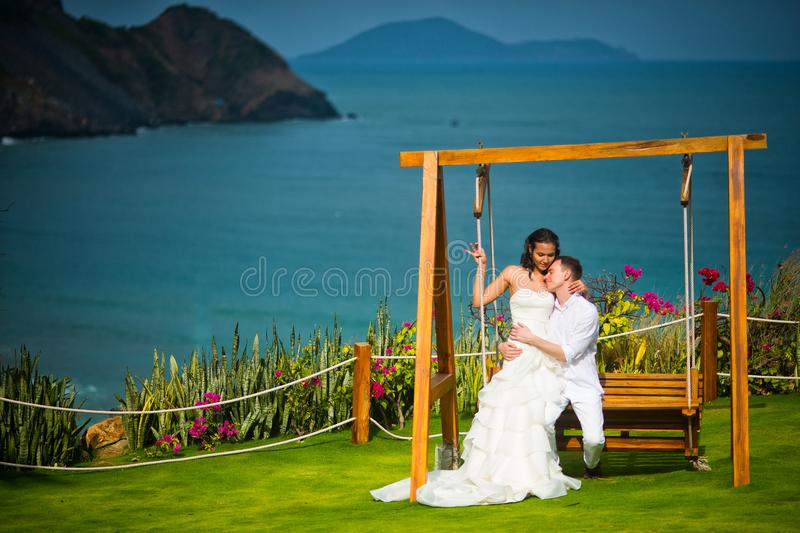 Newlyweds sit on a swing on the background of an incredibly beautiful landscape stock photos