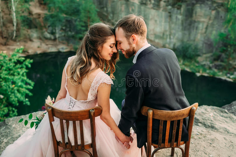 Newlyweds sitting at the edge of the canyon and couple looking each other with tenderness and love. Bride and groom royalty free stock image