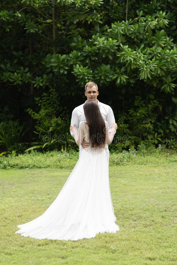 Newlyweds stand on a green lawn against the backdrop of a tropical forest royalty free stock photo