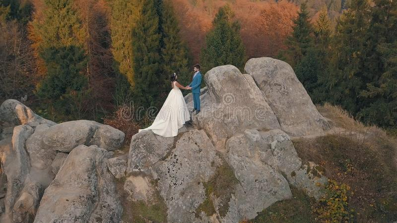Newlyweds stand on a high slope of the mountain. Groom and bride. Arial view royalty free stock photography