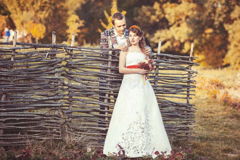 Newlyweds standing near the wicker fence stock photo
