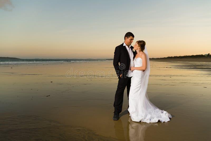 Newlyweds su una spiaggia abbandonata al tramonto fotografie stock
