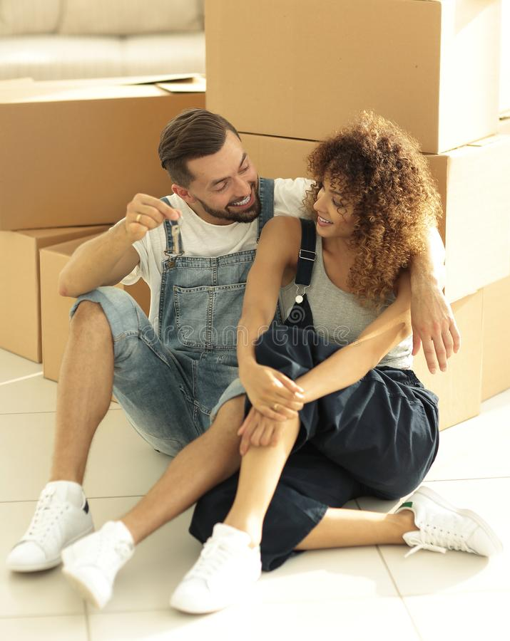 Newlyweds talking while sitting near cardboard boxes stock photography