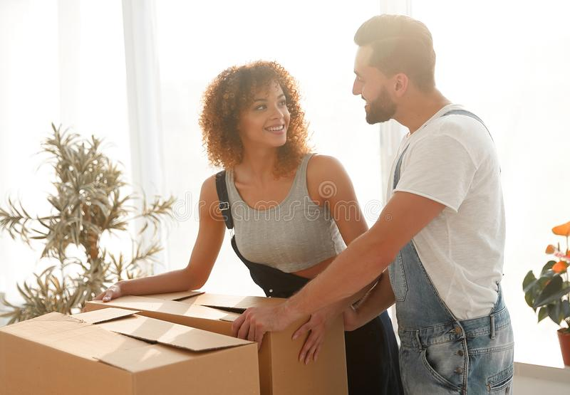 Newlyweds unpack boxes in a new apartment. stock photography