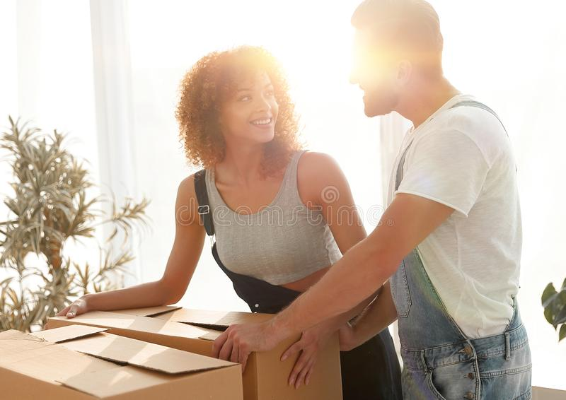 Newlyweds unpack boxes in a new apartment. royalty free stock photo
