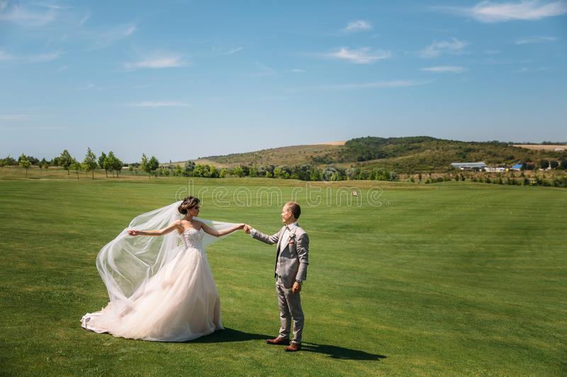The newlyweds are walking along the golf course with green grass. The groom holds the bride`s hand. Beautiful couple on. Wedding day for a walk. Girl in luxury royalty free stock photo