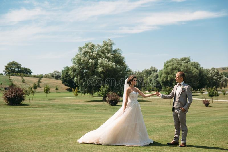 Newlyweds are walking along the green field of the golf club on a wedding day. The groom in a business suit is gray and. The bride in a luxury white dress with stock image