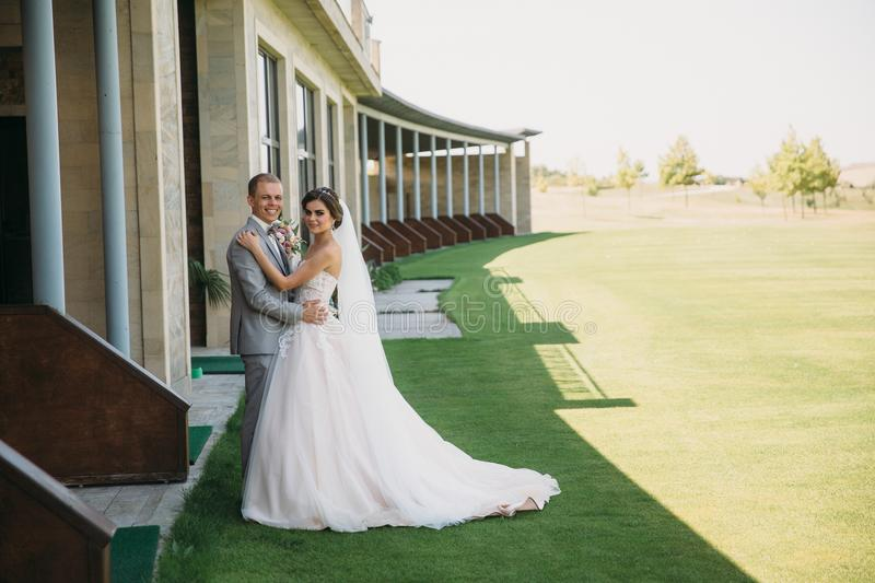 Newlyweds are walking along the green field of the golf club on a wedding day. The groom in a business suit is gray and. The bride in a luxury white dress with stock photo