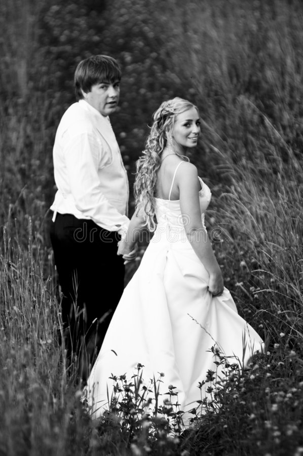 Newlyweds walking in meadow stock photos