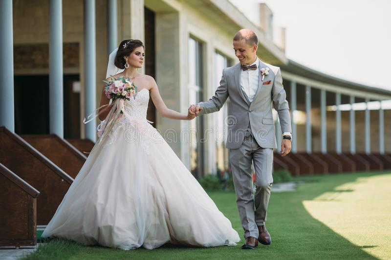 Newlyweds are walking outdoors on a wedding day. The groom in a gray suit with a white shirt and a bow tie holds a. Beautiful bride in her hand with a luxurious stock photography