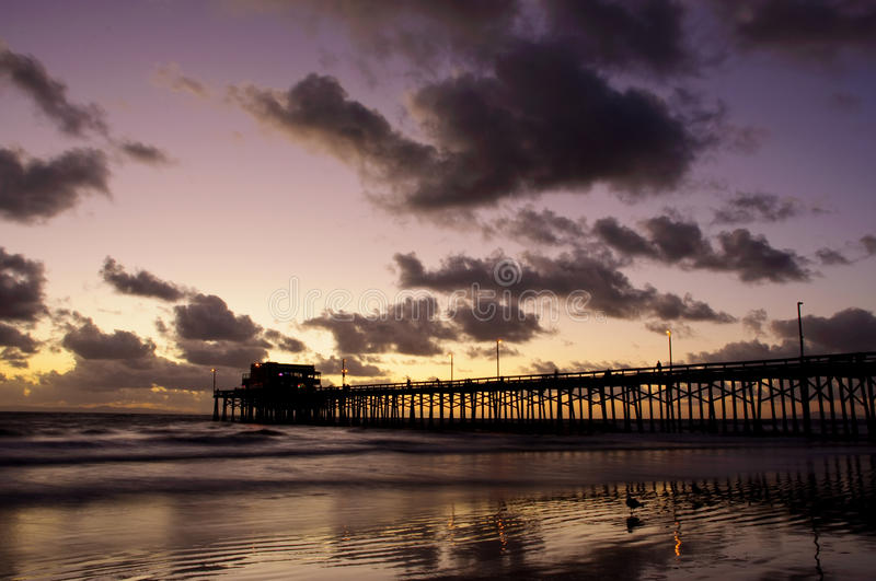 Newport Beach. Sunset in Newport Beach,CA with clouds and reflection on the sand stock photos