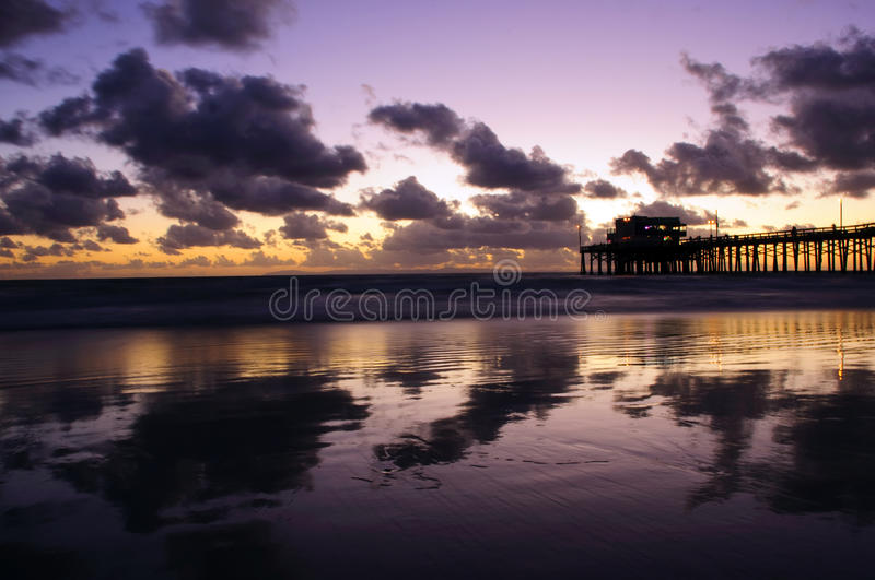 Newport Beach. Sunset in Newport Beach,CA with clouds and reflection on the sand royalty free stock photos