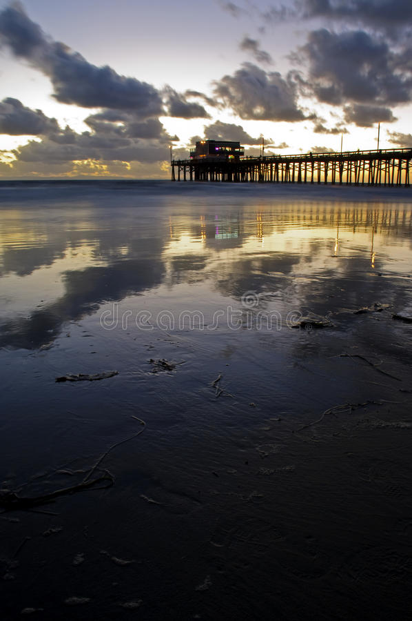 Newport Beach. Sunset in Newport Beach,CA with clouds and reflection on the sand royalty free stock photo
