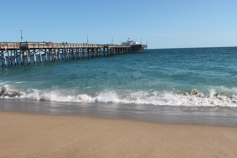 Newport Beach Pier. The Newport Beach pier jutting out into the teal ocean on a warm, calm, summer afternoon against a clear blue sky royalty free stock photos