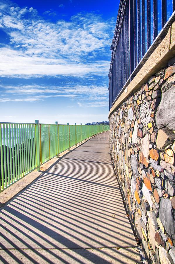Newport Rhode Island Atlantic Ocean cliffwalk. The rocky coast and cliffwalk of Newport Rhode Island in the united states under blue sky and white clouds stock photo