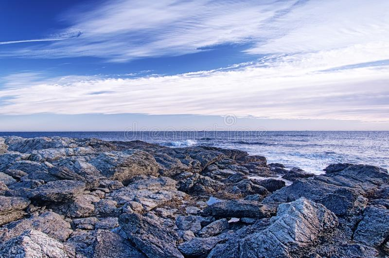 Newport Rhode Island Atlantic Ocean rocky shore. The rocky coast of Newport Rhode Island in the united states at dusk under blue sky and white clouds stock photography