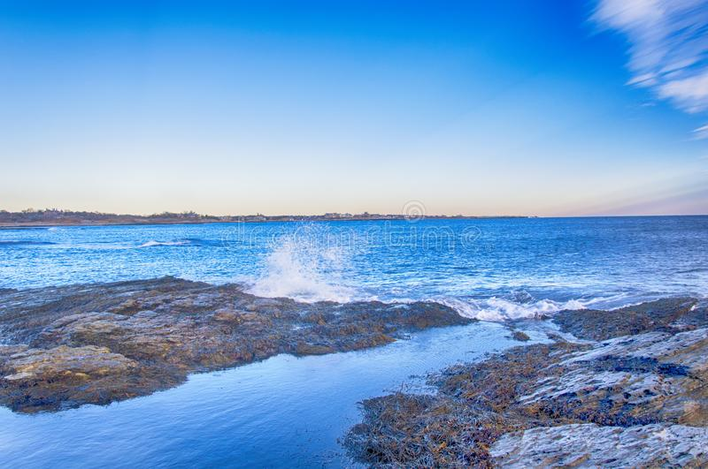 Newport Rhode Island Atlantic Ocean rocky shore. The rocky coast of Newport Rhode Island in the united states at dusk under blue sky and white clouds royalty free stock photography