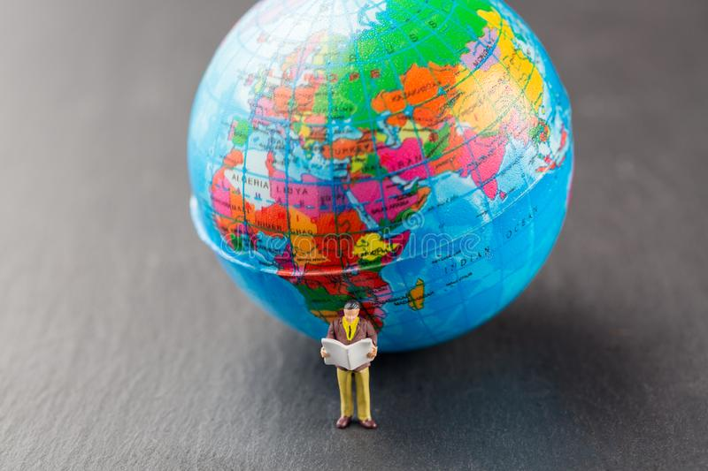 News concept. Miniature business man reading newspaper near world map model globe royalty free stock images