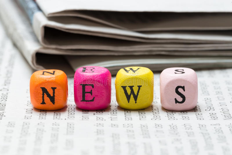 News letter cubes on newspaper macro stock photography