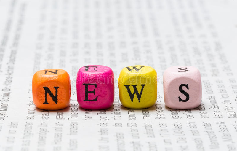 News letter cubes on newspaper macro royalty free stock images