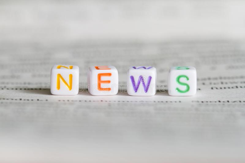 News letters text word on defocused newspaper abstract media macro background. Closeup stock photo