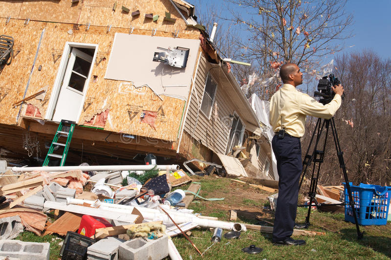 News reporter covering tornado aftermath. LAPEER COUNTY, MI - MARCH 16: WNEM News reporter James Felton videotapes the aftermath of a home heavily damaged by an royalty free stock photo