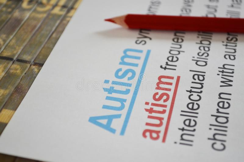 Word AUTISM , close up. Newspaper article and word AUTISM underlined with red and blue pencils stock photos
