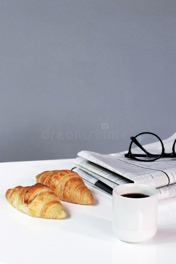 Newspaper break background croissants business with coffee and glasses royalty free stock images
