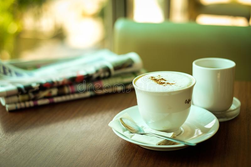Newspaper & Cup of hot coffee cappuccino. Newspaper & Cup of hot coffee cappuccino decorated with powder coffee & milk forth on the surface serve on plate with stock photography