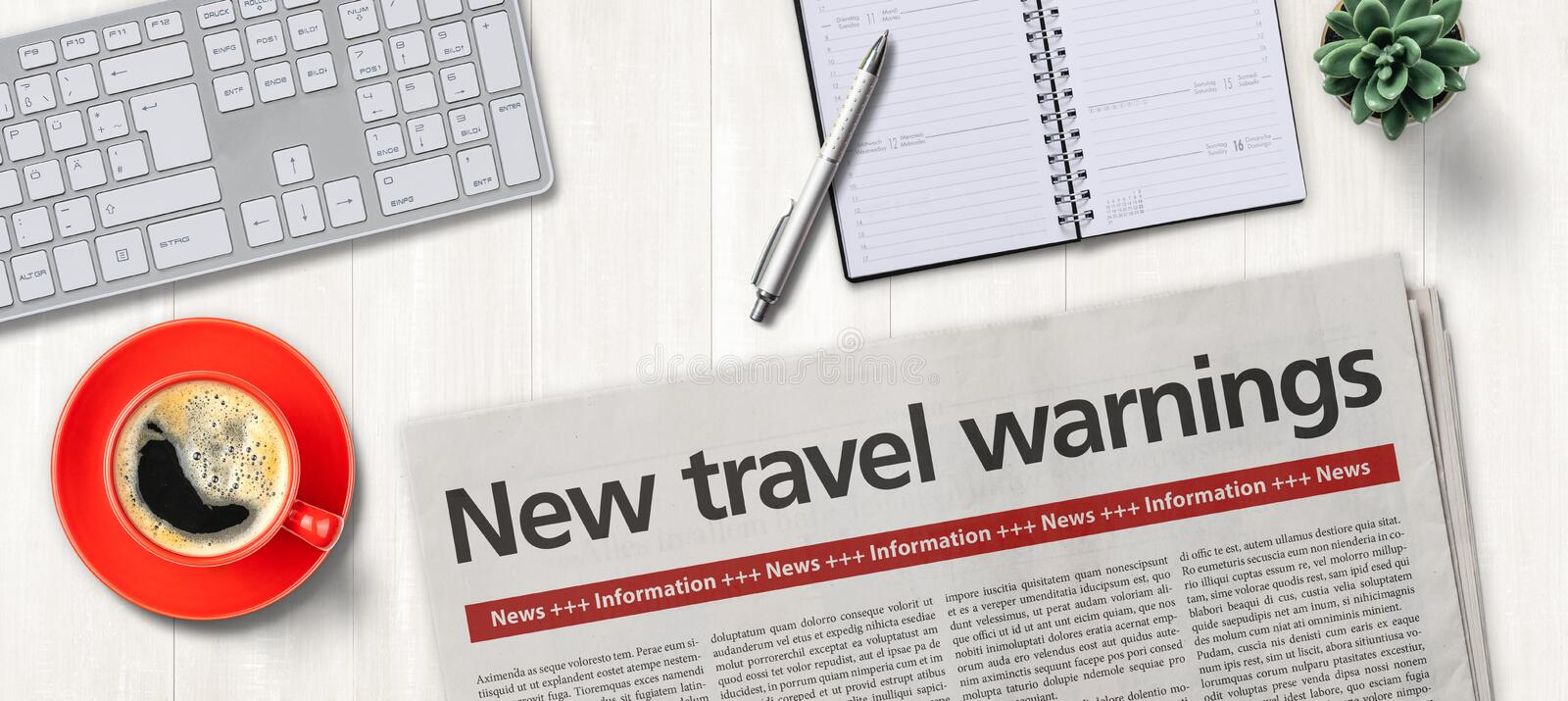Newspaper on a desk -  New travel warnings royalty free stock image