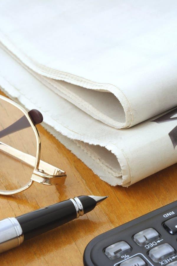 Newspaper, Glasses, Pen and Calculator stock photo