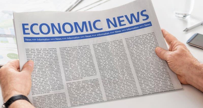Newspaper with the headline Economic News. Man reading newspaper with the headline Economic News stock photos