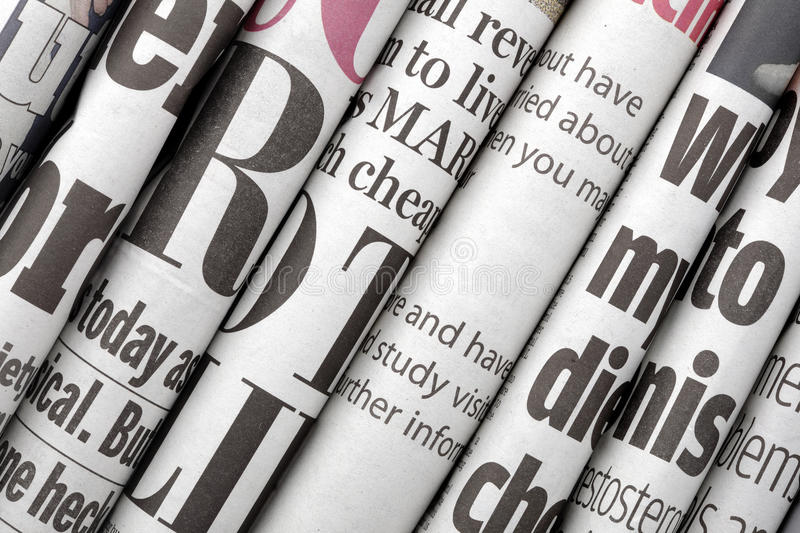 Newspaper headlines. Shown side on in a stack of daily newspapers