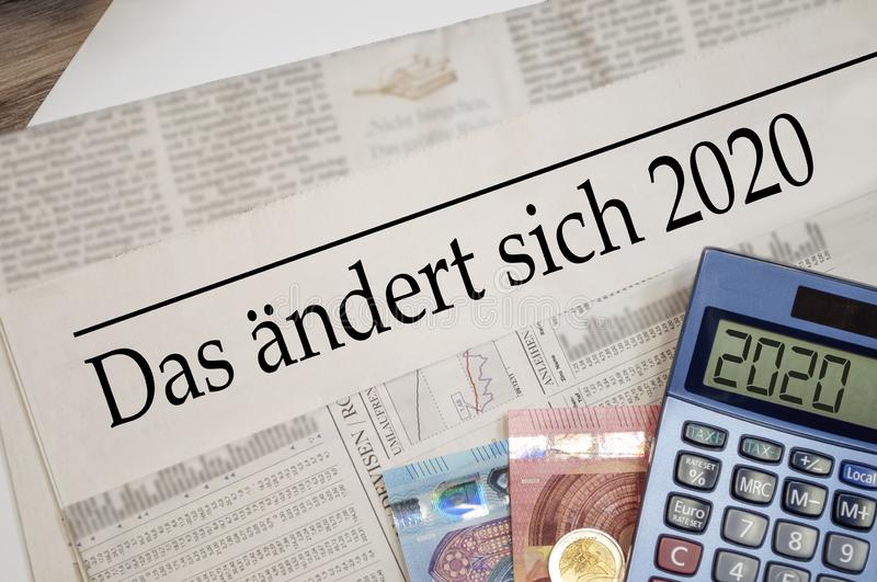 Newspaper with money and calculator and german headline Changes coming in 2020 - das ändert sich 2020. Newspaper with money and calculator and german headline stock photos
