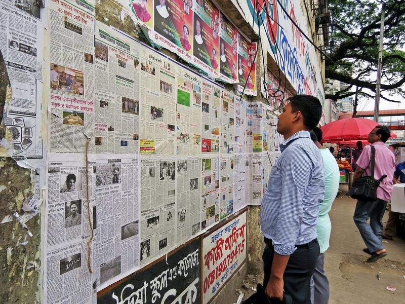 Daily newspaper on the wall in the streets of Dhaka. Locals read their daily newspaper on the wall in a public space in Dhaka, Bangladesh stock photography