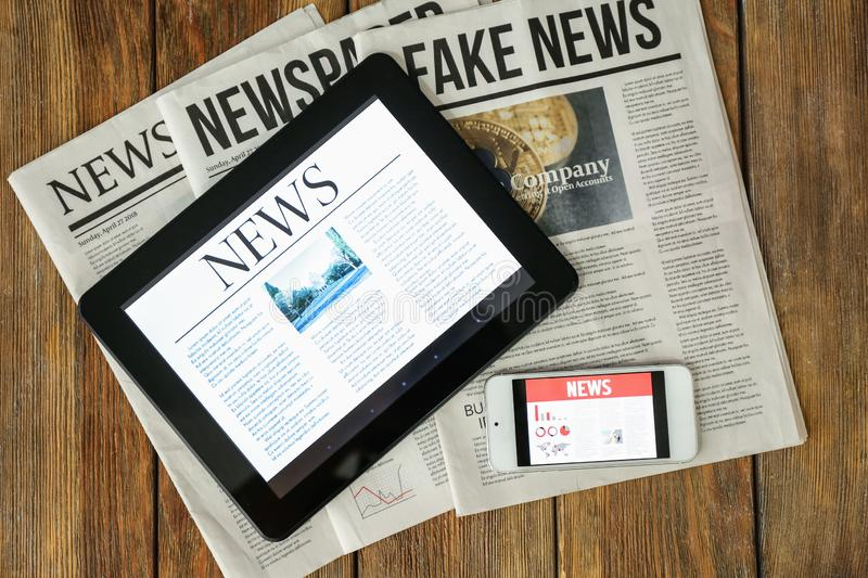 Newspapers, tablet computer and phone with news on screen on wooden table stock images