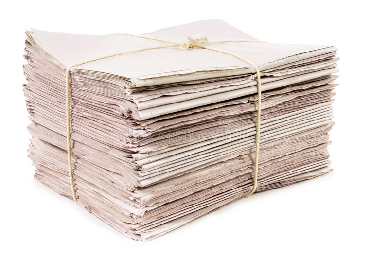Newspapers tied with rope in stack isolated on white background. Bundle of new newspapers tied with rope stock image