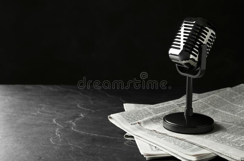 Newspapers and vintage microphone on dark stone table, space for text. Journalist`s work royalty free stock photography