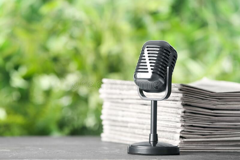 Newspapers and vintage microphone on grey table against blurred green background, space for text. Journalist`s work royalty free stock photo