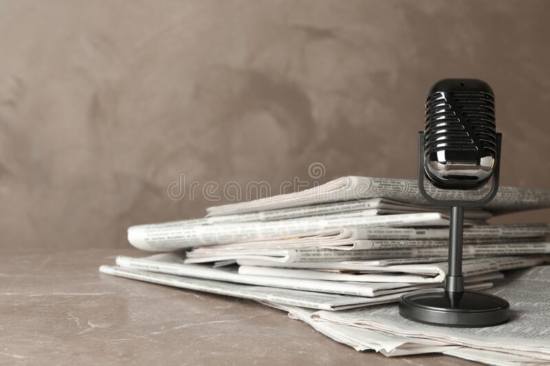 Newspapers and vintage microphone. Journalist`s work. Newspapers and vintage microphone on marble table. Journalist`s work royalty free stock photo