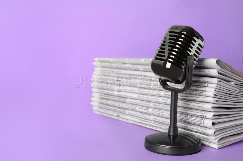 Newspapers and vintage microphone on light violet background, space for text. Journalist`s work royalty free stock image